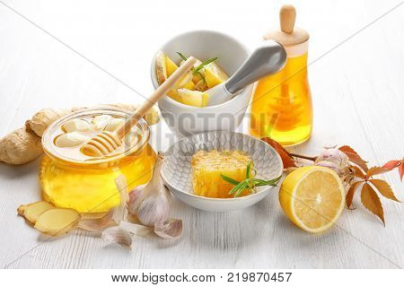 Composition with honey and garlic as natural cold remedies on white wooden background