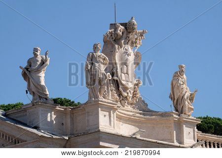 ROME, ITALY - SEPTEMBER 02, 2016:  St. Theobald, Theodore , Alexander VII Coat of Arms and St. Jerome, fragment of colonnade of St. Peters Basilica. Papal Basilica of St. Peter in Vatican, Rome.