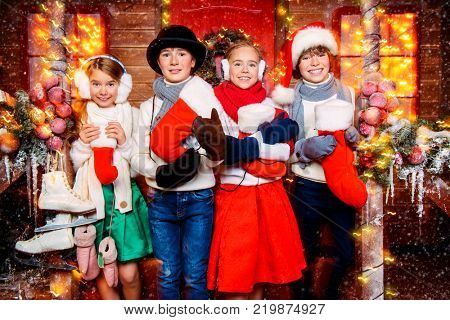 Four cheerful children in winter clothes and accessories stand near the house decorated for Christmas and holding a christmas socks. Time for miracles. Merry Christmas and Happy New Year.