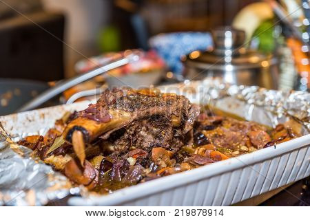 Roasted beef rib steak with bone in roasting tray on busy kitchen table.