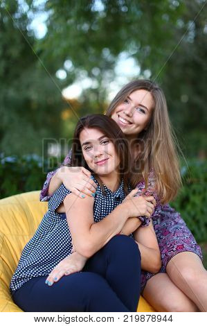 Portrait of two smiling lovely young women of European appearance posing for photo shoot or advertising of cosmetics or clothing catalogs. Women's successful students came to park after school to relax outdoors after hard day. Girl with blonde hair dresse