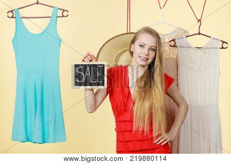 Woman in shop picking summer clothes making perfect outfit holding board with text sale. Fashion good shopping concept.