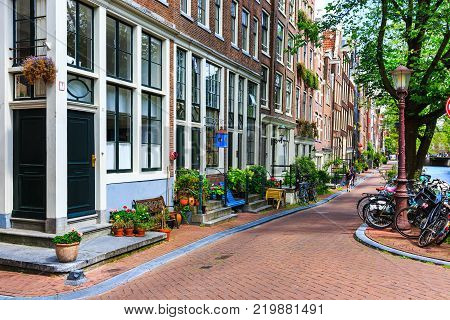 Amsterdam, Netherlands - August 3, 2017: Traditional dutch houses, bicycles parked on city street at summer. Urban landscape with typical holland architecture. Exterior facade buildings, front doors.