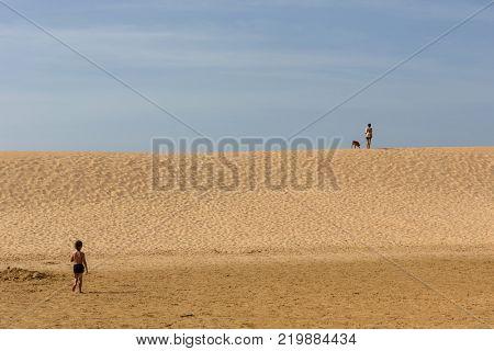PRAIA DA BORDEIRA, PORTUGAL - AUGUST 20, 2017: People at the dunes of the famous beach of Praia da Bordeira. This beach is a part of famous tourist region of Algarve.