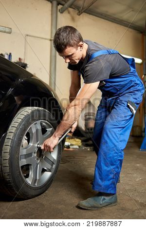 A professional of the automotive car service is tightening the bolts in a tire.