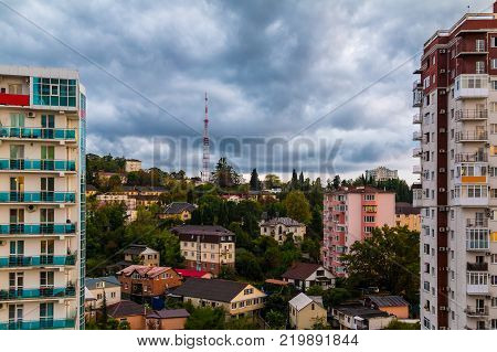 Aerial view of apartment buildings with the beautiful cloudscape with contrasting thudnerclouds, Sochi, Russia