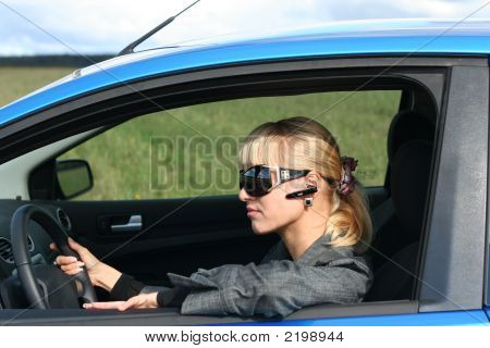 Young Blond Woman In A Blue Car In Sun-Glasses With Hands Free