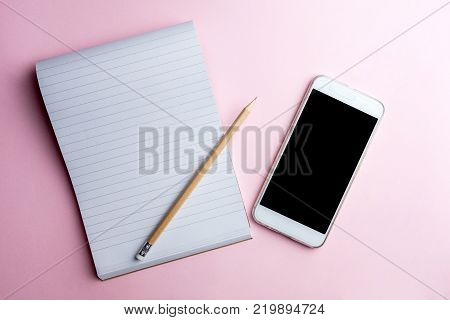 White mobile phone on pink background with note pad and pencil