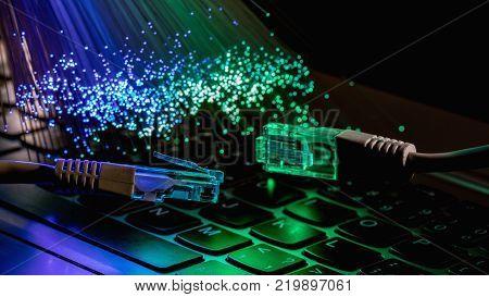 network cable closeup with fiber optical background color fiber optical background with notebookk Fiber optics lights abstract background