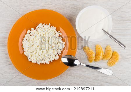 Cottage cheese in orange plate bowl with sour cream slices of tangerine and spoon on wooden table. Top view