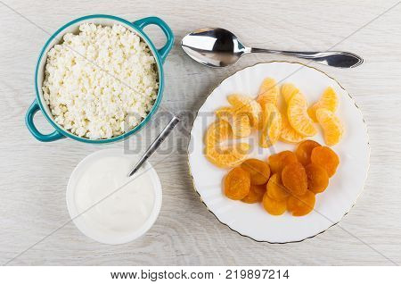 Cottage cheese in bowl plate with tangerines and dried apricots bowl with sour cream spoon on wooden table. Top view