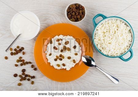 Cottage cheese with sour cream and raisins bowl with sour cream raisins and spoon on wooden table. Top view
