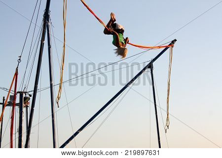 Girl enjoying jumping with ropes on a trampoline