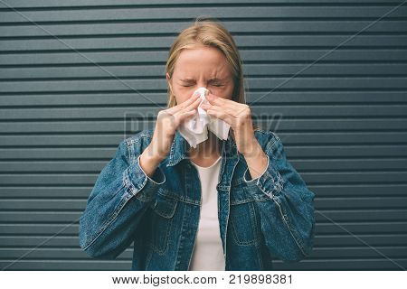picture from a young woman with handkerchief. Sick female model has runny nose