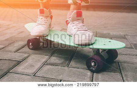 Young skater girl in pink slip on shoes ride colorful tiny skateboard deck outdoors in summer.Sunlight and warm weathe are great for skateboarding in the city, outdoor skate park.Popular sport activity.