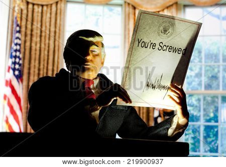 Caricature of United States President Donald Trump holding up an executive order that states: You're Screwed - the new tax plan benefits the wealthy and corporations over the middle class