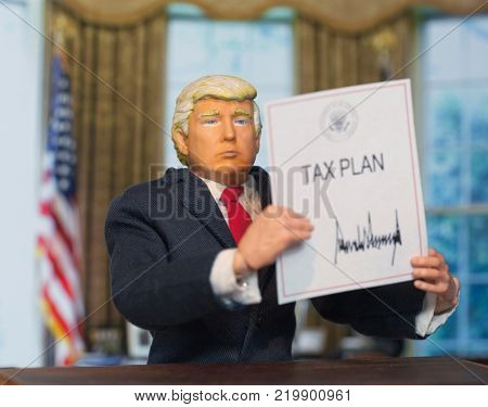 Caricature of United States President Donald Trump holding up an executive order that states: Tax Plan, which was signed as a partisan Republican law