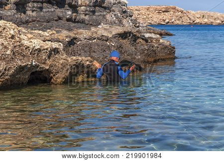 Courage man in the water close to cliff ready for diving adventure fearless