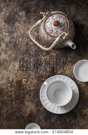 Tea set on a wooden table top view. Teapot empty white tea cup on a brown background top view. Free space for text