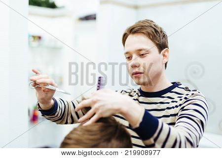 Hairdresser In The Beauty Salon Does A Haircut