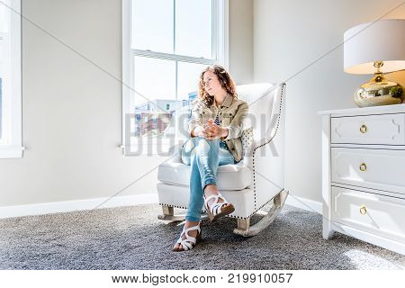 Bright white modern rocking chair in nursery room with chest of drawers, decorations in model staging home, apartment or house, one young woman sitting