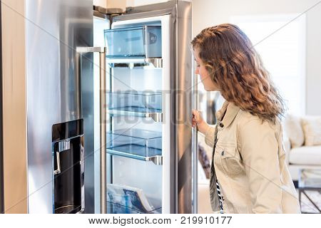 One Young Woman Opening Empty Modern Stainless Steel Chrome Kitchen Refrigerator, Fridge Looking Ins