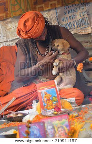 BABUGHAT KOLKATA WEST BENGAL / INDIA - 10TH JANUARY 2015 : Hindu Sadhu cudding a puppy baby street dog.
