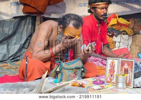 BABUGHAT KOLKATA WEST BENGAL / INDIA - 10TH JANUARY 2015 : Hindu Sadhu making up for rituals wearing bindi a big red dot on forehead.