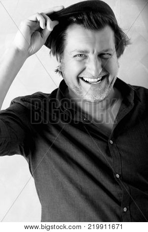 Portrait of a fifty year old man with unbuttoned shirt. He laughs while holding his hat. Balck and white photo