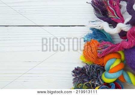 Pet care, veterinary, grooming concept. Pets having fun. A white wooden background with colorful dog toys- rope bones. Space for your text or image.