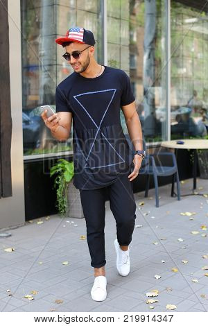 Happy young arabic male man goes on road, smiles and uses phone, manages correspondence with hand in pocket of pants on background of panoramic windows in modern restaurant. Man dressed in dark T-shirt, black pants, white sneakers and black red color cap