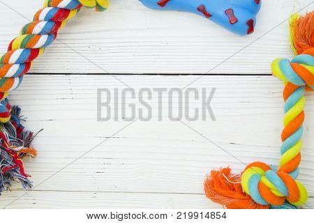 Pet care, veterinary, grooming concept. Pets having fun. A white wooden background with a frame of dog toy rubber and rope bones. Space for your text or image.