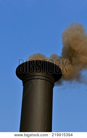 Black smoke billows from the exhaust pipe of a steam engine as steam is also released from the boilers.