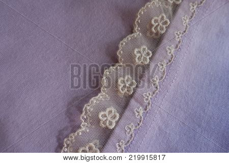 Frill of ivory lace sewn to mauve fabric