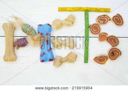 Pet care, veterinary, grooming concept. Pets inscription made of dog and cat toys, chewing bones and snacks on a white wooden background