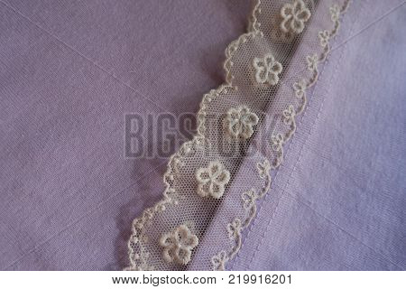 Ribbon of ivory lace sewn to mauve fabric