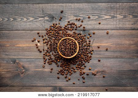 Coffee background. Roasted beans in bowl on dark wooden background top view.