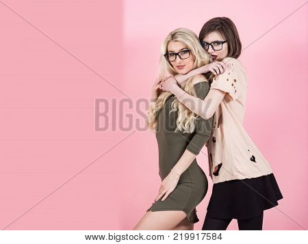 Beauty look concept. Girls pose in torn clothes on pink background. Visage makeup hairstyle. Fashion style vogue. Women with long hair in geek glasses copy space