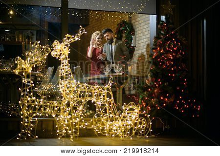 Happy family celebrate new year and christmas. Winter season romance. Woman and man in restaurant with festive decorations. Holidays celebration concept. Couple in love enjoy xmas cuisine food wine.