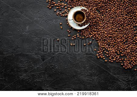 Cup of freshly brewed full-bodied coffee on black table top view copyspace. Coffee background