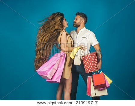 Girl and bearded man hold present pack cyber Monday. Couple in love hold shopping bag near blue wall. Black Friday happy holiday relations. Fashion shopaholic couple. Shopping and sale.