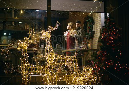 Happy family celebrate new year and christmas. Holidays celebration concept. Couple in love enjoy xmas cuisine food wine. Woman and man in restaurant with festive decorations. Winter season romance.