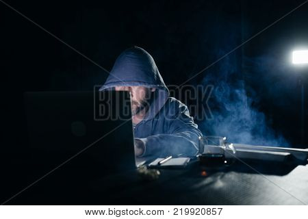 mysterious criminal male hacker doing something illegal on a laptop in the dark