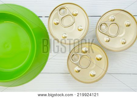 Pet care, pet food concept. Feeding your pet friend. An empty green plastic bowl and three tin cans of pet food , close up. White wooden background.