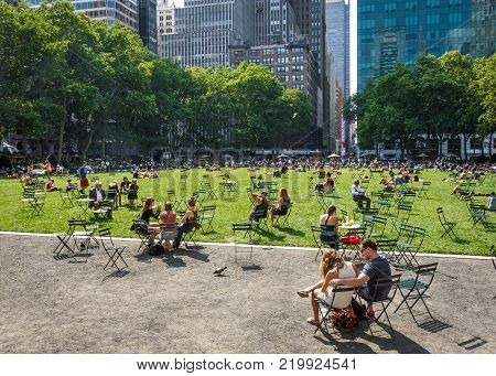 NEW YORK-JUNE 9: People relax on a beautiful late Spring day in Bryant Park on June 9 2015 in midtown Manhattan.
