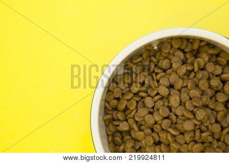 Pet care feeding concept. A nutritious healthy food for a pet. A bowl of dry pet food on a bright yellow background, close up. Top view. Space for your text or product display.