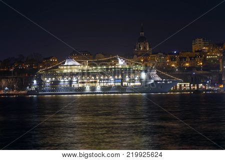 STOCKHOLM SWEDEN - DEC 27 2017: Nightscape of a large ferry and beautful architecture in central Stockholm in Sweden December 27 2017
