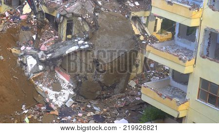 the process of destruction of the old building with heavy machinery.