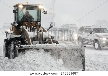 Front End Wheel Loader removes snow from road during heavy snow winter storm, poor visibility. Winter highway maintenance in Petropavlovsk-Kamchatsky City. Kamchatka Peninsula, Russian Far East.