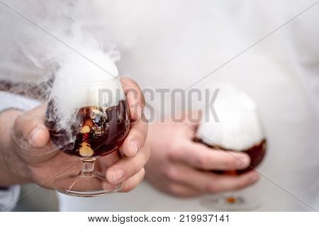 Men's hands holding a glass with alcoholic beverages with dry ice making a heavy vapor